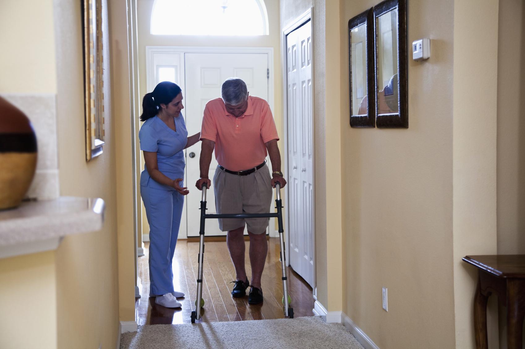 Home healthcare - Hispanic nurse at home of senior man (60s) using walker.